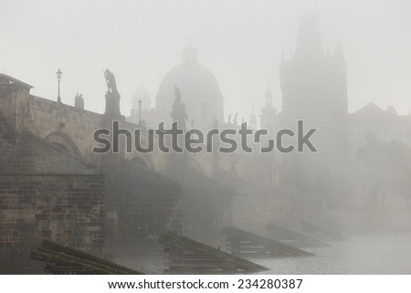 Autumn Prague gothic Charles Bridge with the Oldtown in the morning Fog, Czech Republic - stock photo