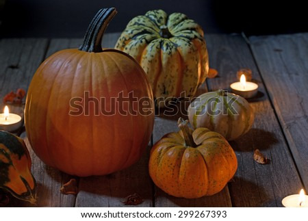 Autumn pumpkins and squash at night lit by candles - stock photo