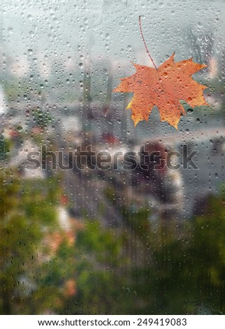 Autumn, rainy city through a window with raindrops. autumnal mood. - stock photo