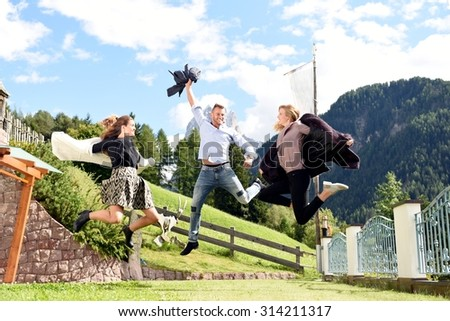 Autumn, rich, nature and teenage lifestyle concept - group of young friends jumping on mountain resort. Portrait of elegant two beautiful young women and a man having fun outside in autumn clothes.  - stock photo