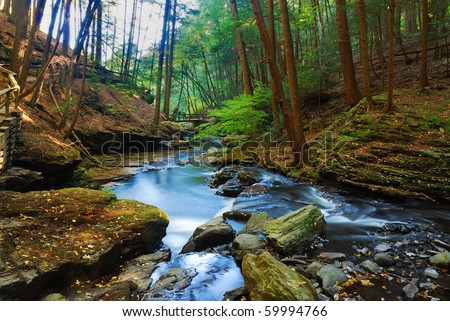 Autumn River in forest with foliage and rocks. - stock photo