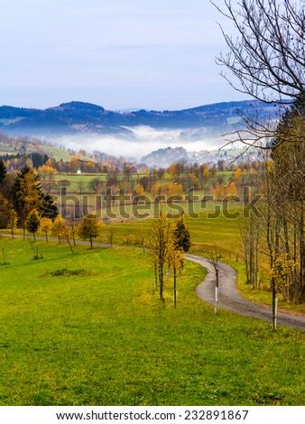Autumn road in mountains - stock photo