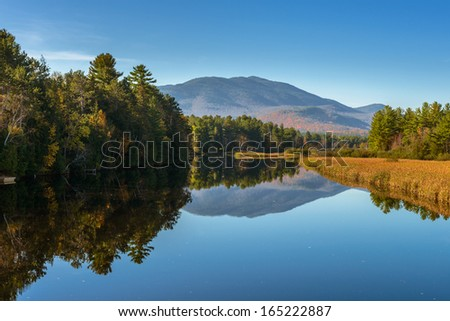 Autumn scenery at sunrise reflected in the water of the river - stock photo
