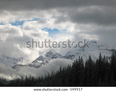 autumn snowstorm clearing out of the mountains - stock photo