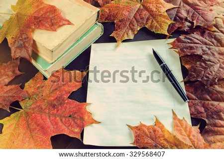Autumn still life in vintage tones -  old books near yellowed sheet of paper and old vintage ink pen on the table among yellow maple leaves.  Selective focus at the ink pen - shallow depth of field - stock photo