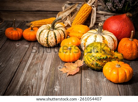 Autumn still life with pumpkins and leaves on old wooden background - stock photo