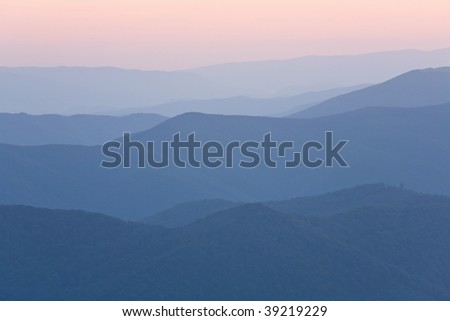 Autumn sunrise mountain view with haze and forest - stock photo
