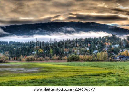 Autumn sunrise over Salmon Arm in the Canadian Rockies, illuminating a splendor of fall colors in the popular townsite. - stock photo