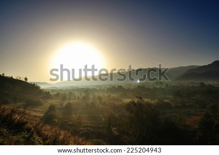 Autumn sunrise with fog on the ground. - stock photo