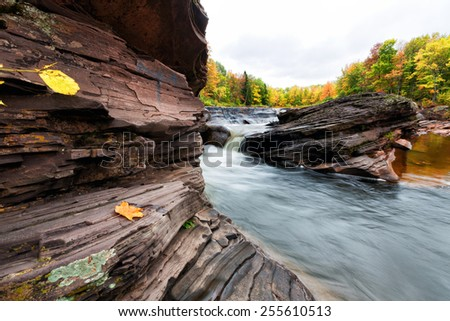 Autumn surrounds Bonanza Falls in the Upper Peninsula of Michigan. This waterfall is on the outskirts of the Porcupine Mountain Wilderness area. - stock photo
