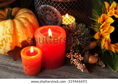Autumn thanksgiving decor with pumpkin candle and sunflower  - stock photo