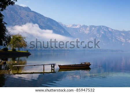 Autumn time at lake in valley in Slovenian Alps. - stock photo