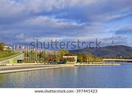 autumn trees on a wateredge of Lake Burley Griffin in Canberra under warm morning sun with Flags in background. - stock photo