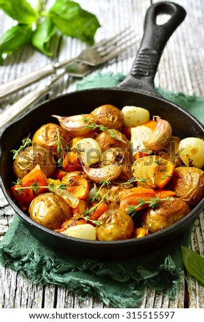 Autumn vegetable roast with herbs in a skillet pan. - stock photo