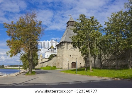 Autumn view of ancient Kremlin and its powerful tower, in Pskov, Russia with trees and Trinity Cathedral on the background - stock photo