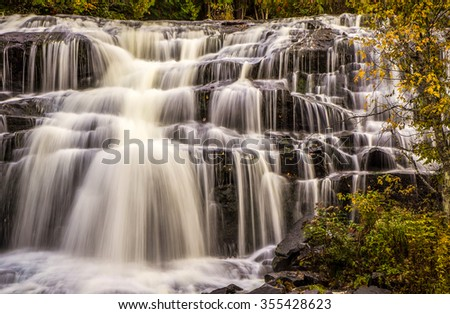 Autumn Waterfall Background. Beautiful Bond Falls with autumn leaves flowing with the clear waters. Bond Falls. Paulding, Michigan. - stock photo