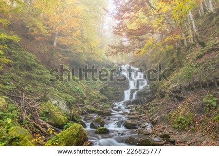 Autumn waterfall in foggy forest - stock photo