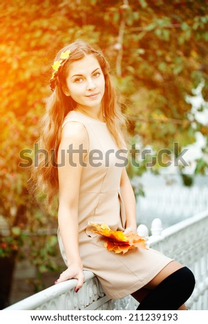 Autumn woman. Beautiful young trendy girl in autumn park.  - stock photo