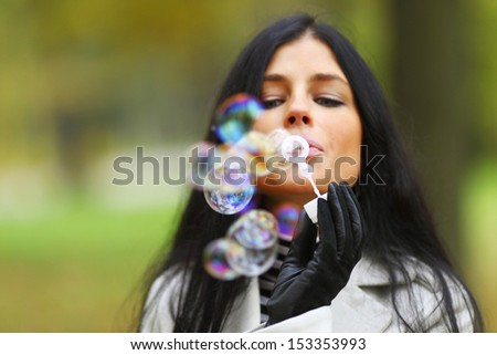 autumn woman blow bubbles portrait in park - stock photo