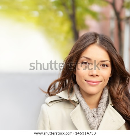 Autumn woman portrait in fall outdoors. Beautiful multi-ethnic girl brunette with long dark hair smiling happy looking at camera. Mixed race Chinese Asian / Caucasian female model. - stock photo