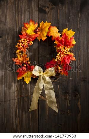 Autumn wreath hanging on a wooden door - stock photo