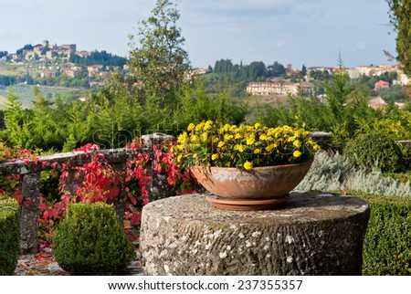 Autumn yellow flowers on the terrace of old Tuscan villa over view of Old town Panzano in Chianti. - stock photo