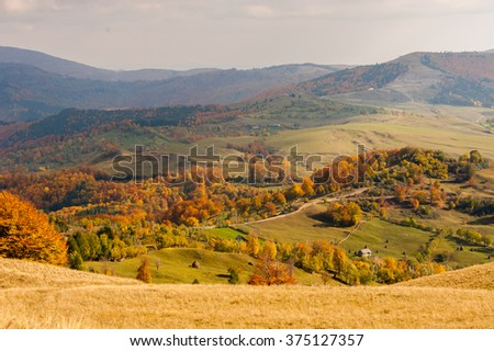 Autumnal mountain landscape with houses. Beautiful sunny autumn mountains panoramic view of rural rustic mountain village, rustic fences, sunny colorful forest. - stock photo