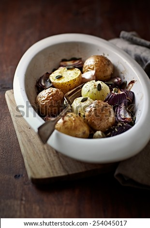 Autumnal potatoes and onions with garlic and green pumpkin seeds - stock photo
