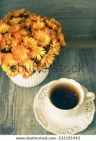 Autumnal table setting with bunch of autumn flowers and cup of - stock photo