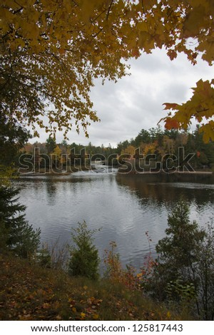 Autumnal tree branches overhang a calm body of water - stock photo