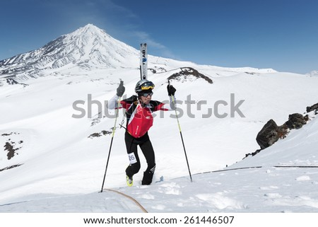 AVACHA VOLCANO, KAMCHATKA, RUSSIA - APRIL 26, 2014: Alex Maltsev climbs a mountain on background of the Koryak Volcano. Individual race ski mountaineering Asian, ISMF, Russian, Kamchatka Championship. - stock photo