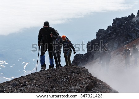 AVACHA VOLCANO, KAMCHATKA, RUSSIA - JULY 08, 2014: Hiking on Kamchatka - a group of tourists climbing to the top crater of active Avachinsky Volcano on Kamchatka Peninsula (Russian Far East). - stock photo