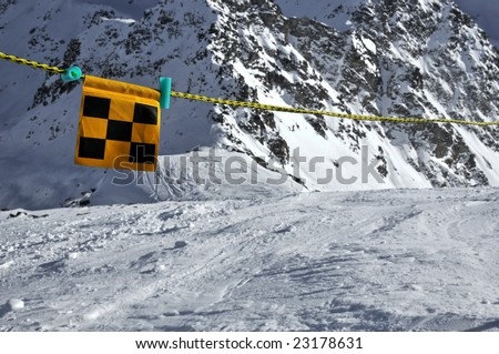 Avalanche danger flag intending to barr the way for safety reasons, but skiers have ignored it. - stock photo
