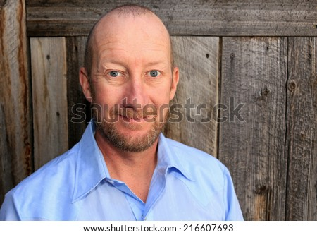 Average middle aged man with a wooden background. - stock photo