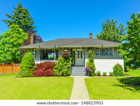 Average North American family house on a sunny day. Family house with looking through windows in the living room. - stock photo