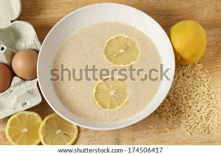 Avgolemono soup - made with chicken broth, lemon, egg and rice-shaped pasta. This is a very traditional Greek dish. - stock photo
