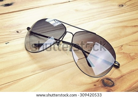 Aviator sunglasses on a wooden board, Classic sunglasses. (Vintage Style Color) - stock photo