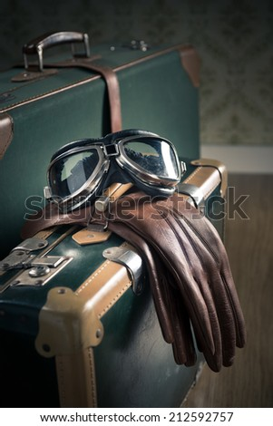 Aviator vintage glasses and leather gloves and suitcases on the floor. - stock photo