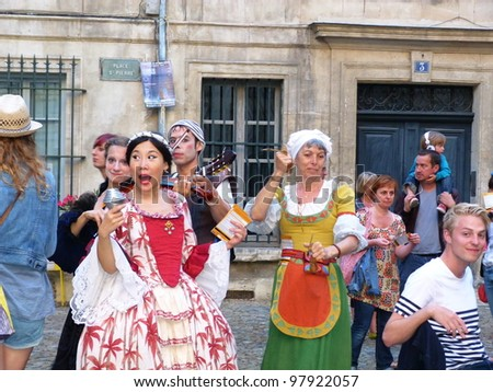 AVIGNON, FRANCE - JULY 17: Unidentified theater actors perform in a square, to advertise their theater show, during annual Avignon Theater Festival in Avignon, France on July 17, 2011. - stock photo