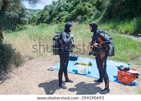 AVLAKI,GREECE-JULY 04 2015 :Two female Scuba Divers have a safety brief before they go for a dive.Diving is an adventurous sport with dive sites in most countries around the world. - stock photo