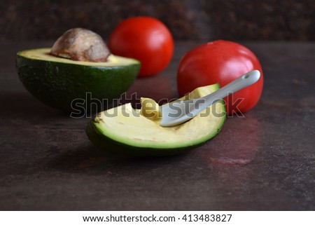 Avocado and tomatoes are on the dark background. A spoon with avocado. - stock photo