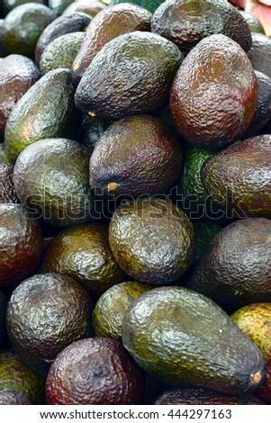 Avocado background. Fresh green avocado on a market - stock photo