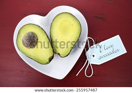 Avocado cut in half on heart shape plate on dark red vintage rustic wood table, with I Love Avocados text sign. - stock photo