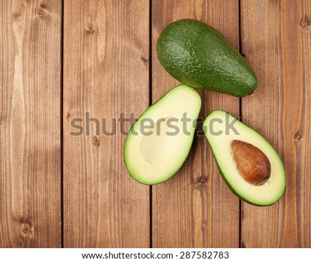 Avocado fruit lying over the brown colored wooden board surface as a background composition - stock photo