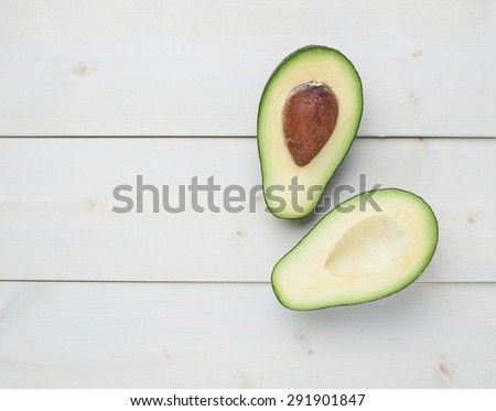 Avocado fruit lying over the white colored wooden board surface as a background composition - stock photo