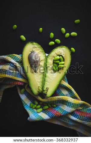 avocado fruit on a dark background with soy beans called edamame - stock photo