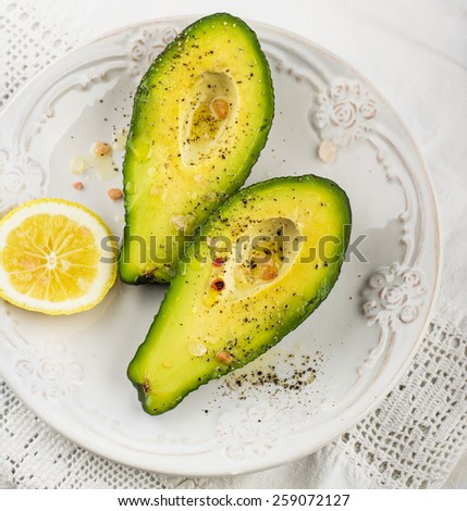 avocado halves with butter salt and pepper on a white ceramic plate with a slice of lemon - stock photo