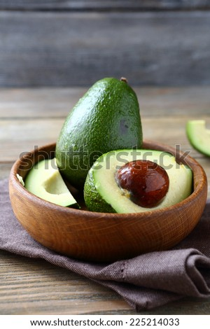 avocado in a wooden bowl, food close up on a napkin - stock photo