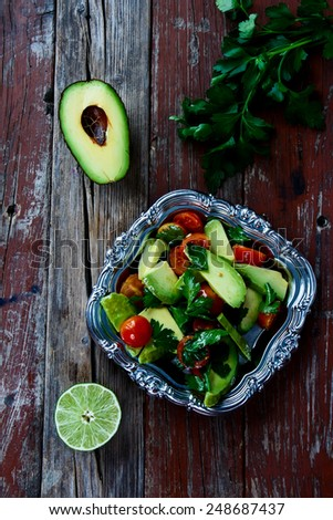 Avocado salad in vintage metal plate - healthy food, diet or cooking concept. Top view. - stock photo