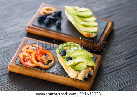 Avocado sandwich with blueberries and tomato garnish - stock photo